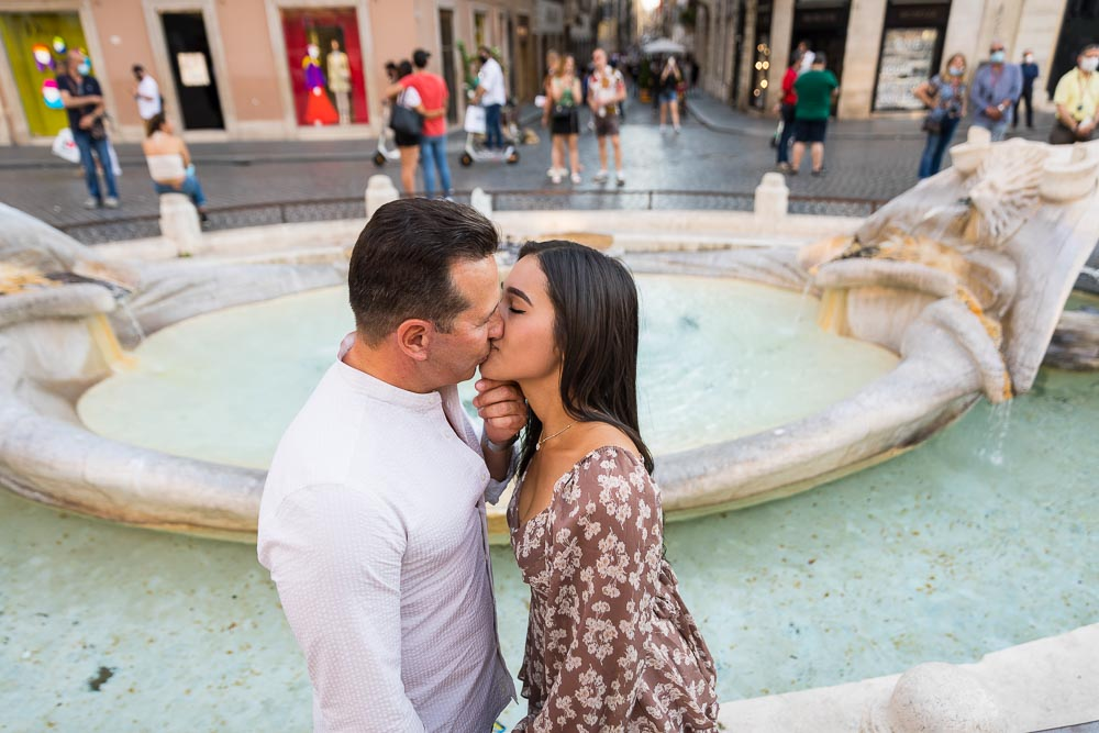 A romantic kiss taken by the water fountain found at the bottom of Piazza di Spagna