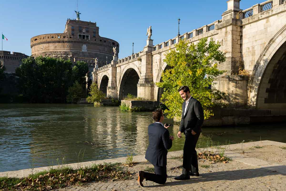 Knee down Same Sex Wedding Marriage Proposal in Rome candidly photographed on the Tiber river bank with the unique view of the Castel Sant'Angelo castle in the background