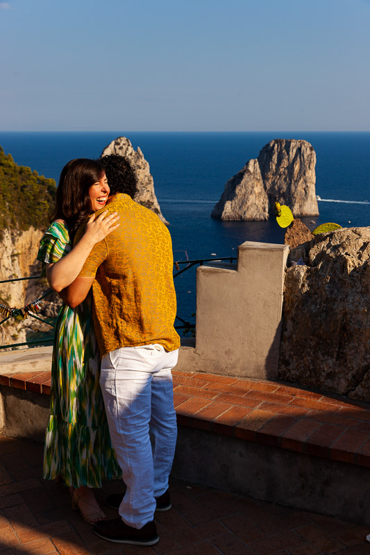 She said yes moment photographed from afar with the faraglioni rocks in the background