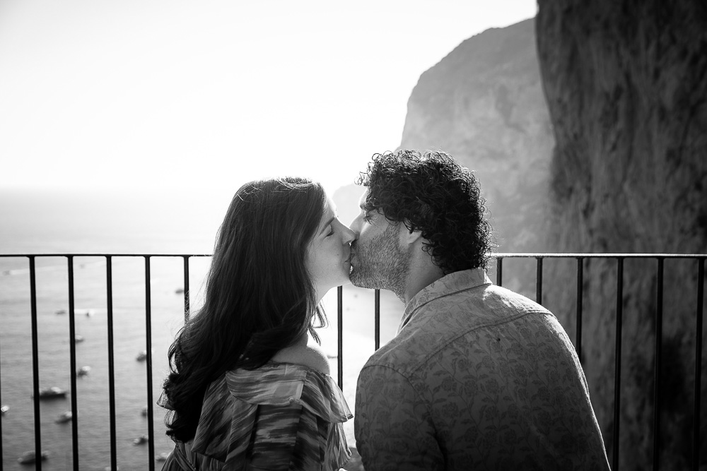 Couple kissing at sunset before an amazing view of the Italian sea. Image in black and white