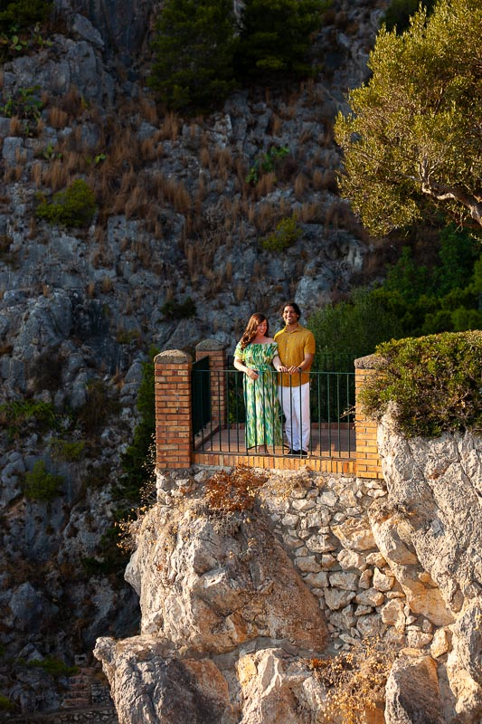Couple portrait taken from posing in front of camera from the other side of the costal terrace