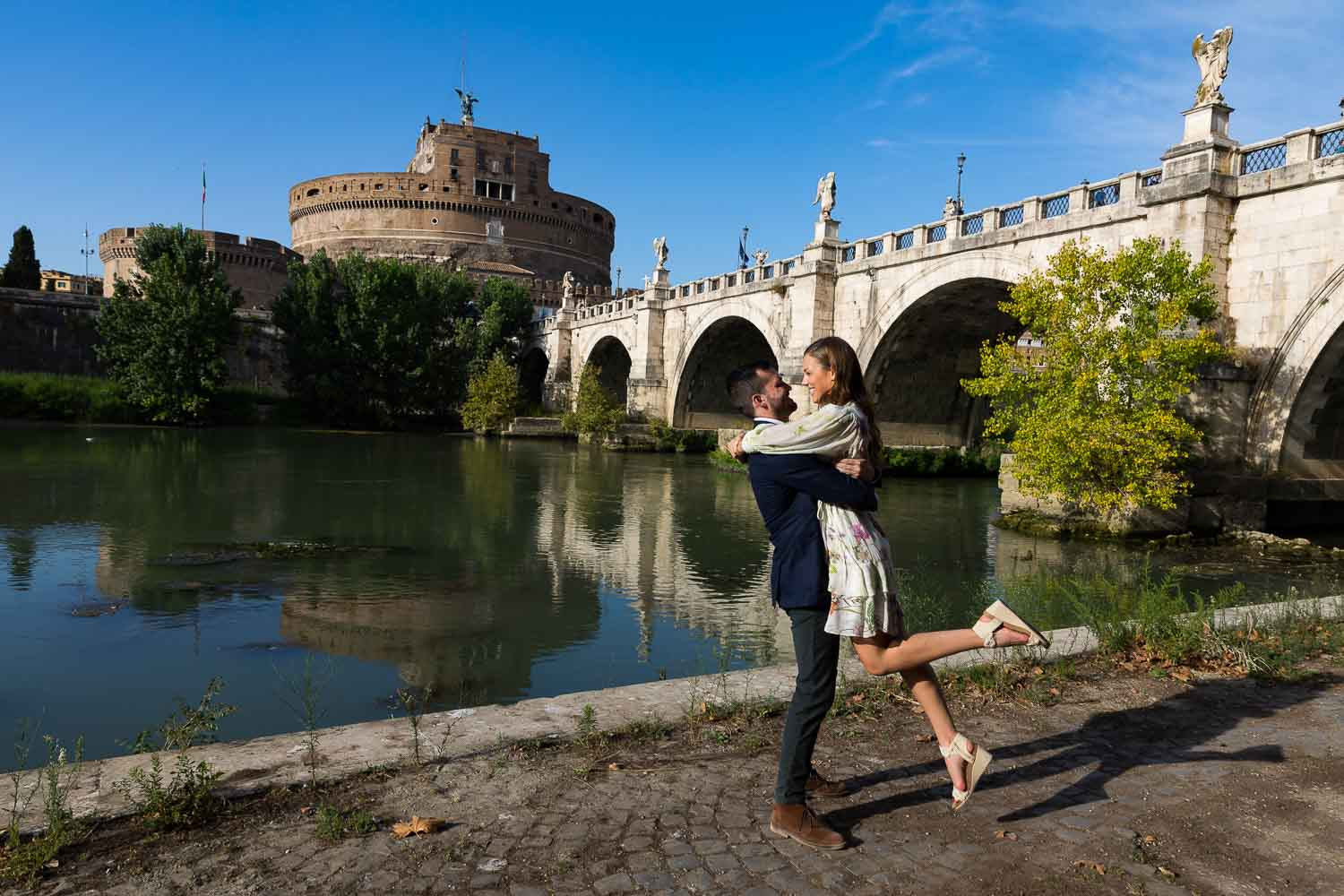 Jumping for joy at the Castel Sant'Angelo bridge next to the Tiber river bank