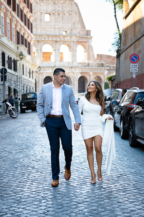 Couple walking on cobblestone alleyways in the streets of Rome with the Roman Colosseum as unique backdrop